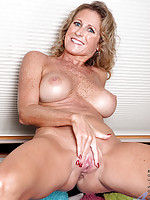 Busty Anilos beauty strips and fingers her mature shaved pussy